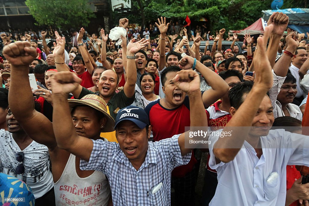 National League for Democracy party supporters cheer as they gather to hear first election results outside the party headquarters in Yangon Myanmar...