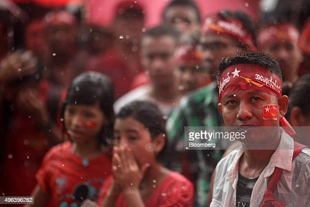 National League for Democracy party supporters stand as heavy rain falls outside the party headquarters in Yangon Myanmar on Monday Nov 9 2015 The...