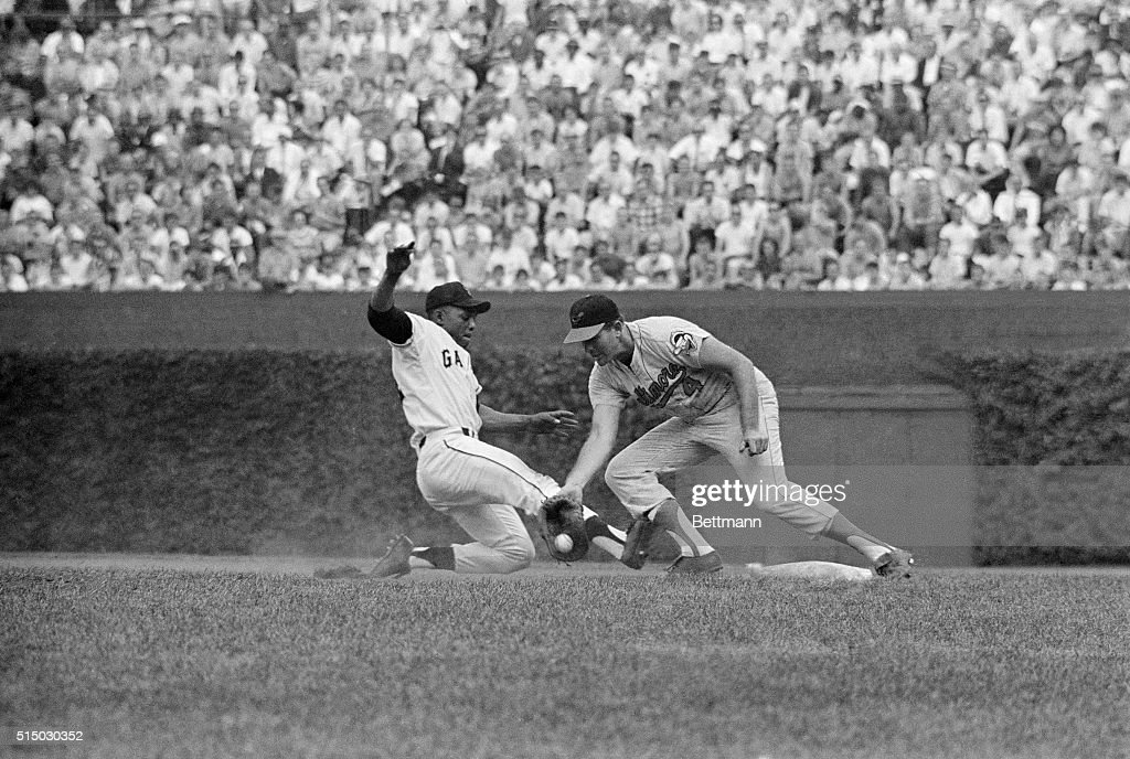 National League's Willie Mays hustles back to 1st to beat 'pickoff attempt' by American League pitcher Ray Herbert here as 1st baseman Jim Gentile...