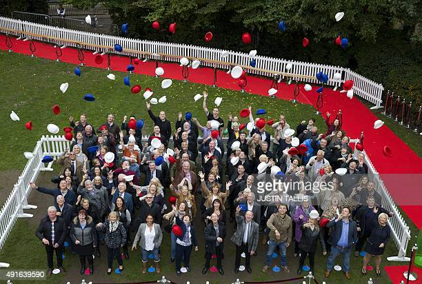 National lottery winners raise their hats as they gather for a photo call in in London on October 7 to aim to set a new world record for the largest...