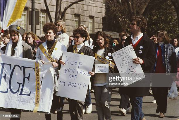 A National March for Women's Lives in Washington DC 9th March 1986 One prochoice protestor holds an image of a bloody coat hanger with a cross...