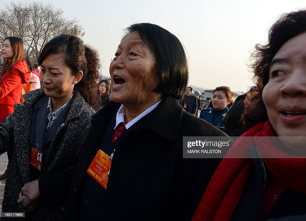 National Model Worker and NPC delegate for 55 years, Shen Jilan (C) from Shanxi Province, who is famous for voting 'yes' and supporting the party on every NPC proposal, arrives for the opening session of the National People's Congress (NPC) at the Great Hall of the People in Beijing on March 5, 2013. Thousands of delegates from across China were meeting this week to seal a power transfer to new leaders whose first months running the Communist Party have pumped up expectations with a deluge of propaganda. AFP PHOTO/Mark RALSTON