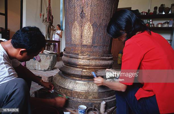 National Museum technician Thlang Sakhoeun in red works with another museum employee to restore a royal funeral urn discolored and filled with...