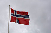 norwegian flag on flagpole at cloudy day
