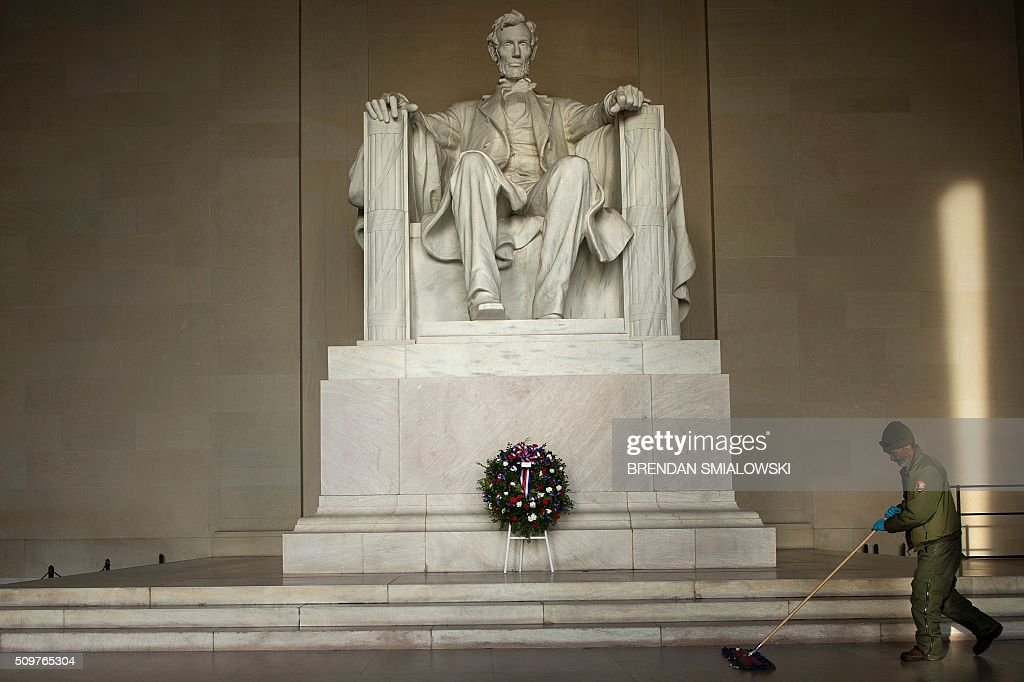 National Park employee cleans the floor of the Lincoln Memorial after a wreath-laying ceremony to honor Abraham Lincoln's 207th birthday February 12, 2016 in Washington, DC. / AFP / Brendan Smialowski