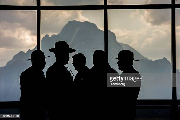 National Park Rangers stand silhouetted inside the lobby of Jackson Lake Lodge during the Jackson Hole economic symposium sponsored by the Federal...