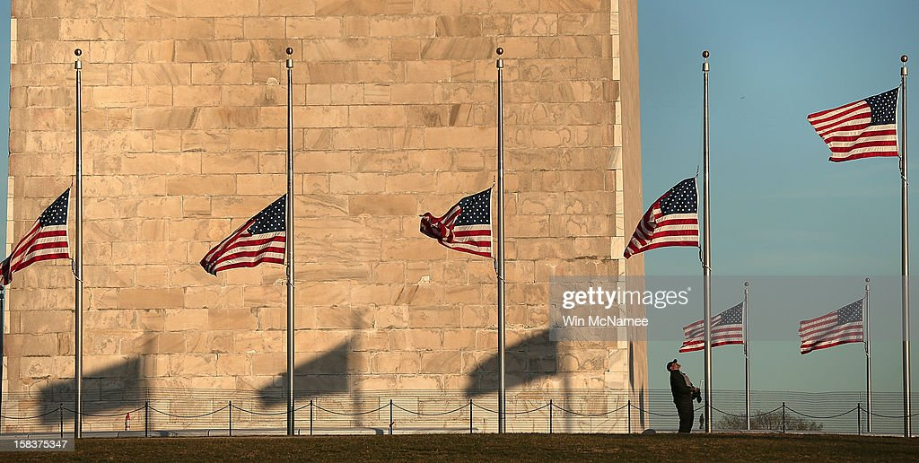 A National Park Service employee lowers flags at the base of the Washington Monument to half staff after President Barack Obama ordered the action while speaking on the shootings at the Sandy Hook Elementary School December 14, 2012 in Washington, DC. Obama called for 'meaningful action' in the wake of the latest school shooting that left 27 dead, including 20 children.