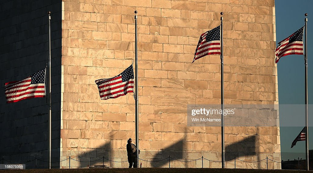 National Park Service employee lowers flags at the base of the Washington Monument to half staff after President Barack Obama ordered the action...