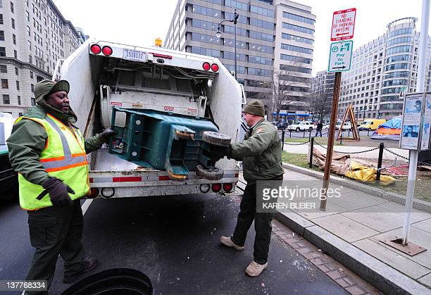 National Park Service employees Garey Bickham and George Stinnie hoist a cart full of trash into the back of a garbage truck at the Occupy DC...