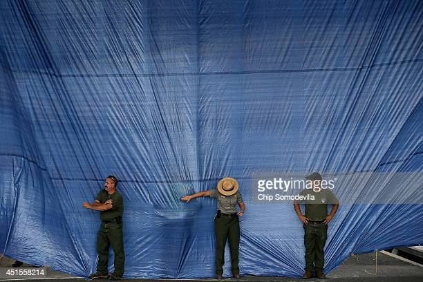 National Park Service employees work to keep the wind from blowing open a curtain of blue plastic tarps underneath the Whitehurst Freeway overpass...