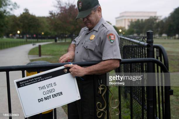 National Park Service park ranger Richard Trott removes a closed sign near the Lincoln Memorial in Washington DC US on Thursday Oct 17 2013 After the...