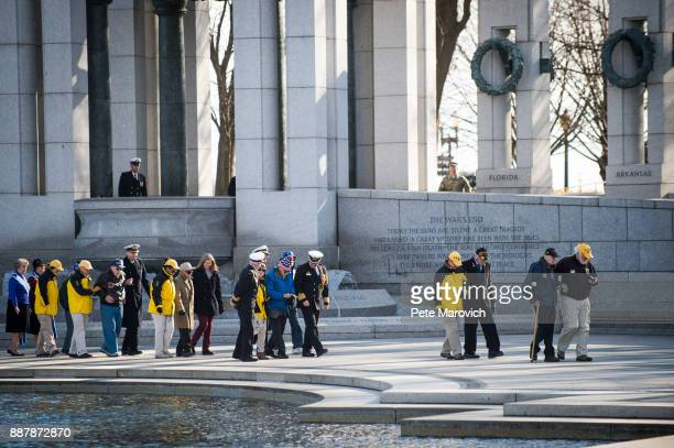 National Park Service volunteers escort WWII veterans to the wreath laying ceremony held by the Friends of the National World War II Memorial and the...