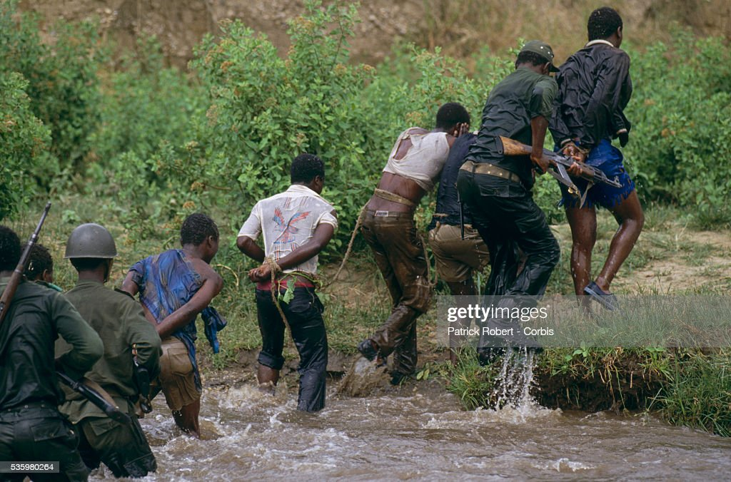 National Parks Guards cross a river in Zaire with a group of poachers who have been arrested and bound together. The national parks continue to struggle against the poaching of elephants and the traffic of ivory in Zaire (later the Democratic Republic of Congo).