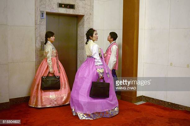 National People's Congress staff dressed as minorities wait for the elevator at the Great Hall of the People during the 3nd plenary session of the...