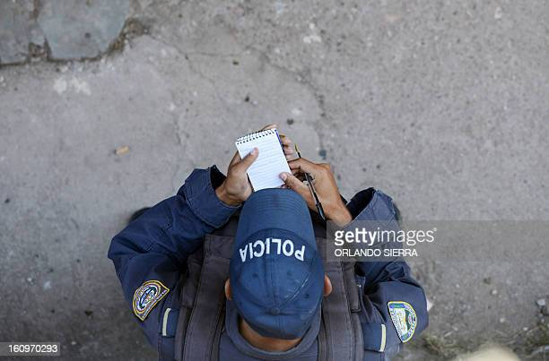 A National Police officer takes notes as he patrols the streets of Tegucigalpa on February 8 2013 in a joint operation with the Honduran Army to...