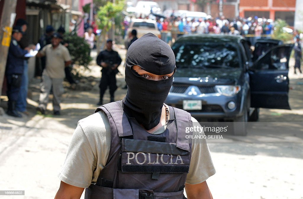 A National Police officer works at the crime scene in which five people -- including a high school student -- were shot dead in the suburb of La Haya, in northern Tegucigalpa, on April 15, 2013. In March 2012, the UN announced Honduras had the world's highest murder rate, at 82.1 deaths per 100,000 people, while a local observatory on violence put the rate at 86.5 per 100,000. AFP PHOTO/Orlando SIERRA