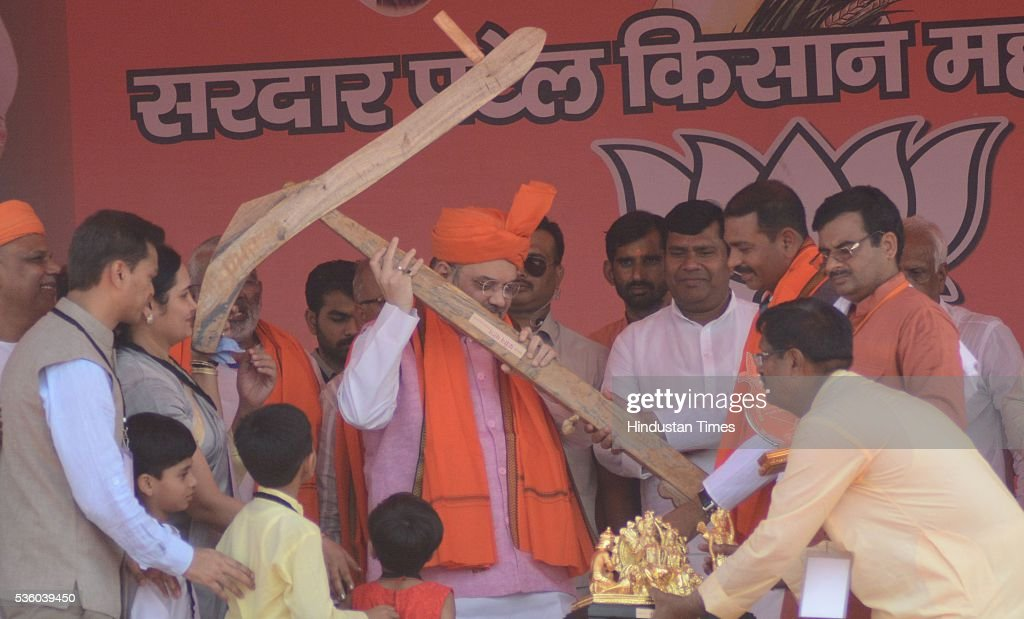 National President Amit Shah presented with plough during the Sardar Patel Kisan Mahasammelan at Andawa area in Jhunsi on May 31, 2016 in Allahabad, India. On his way to rally, BJP chief Amit Shah had lunch with Dalit and backward class members in a dusty village in Varanasi. The event was not elaborate but the symbolism was hard to miss that party is reaching out to caste groups not counted among its core supporters ahead of the crucial 2017 assembly election in Uttar Pradesh.