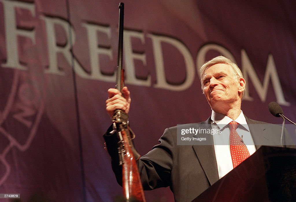 National Rifle Association (NRA) President Charlton Heston holds up a rifle during his address at the 131st NRA convention at the Reno-Sparks Convention Center in Reno, Nevada, April 27, 2002. Heston announced that he would remain president of the NRA for an unprecedented fifth term.