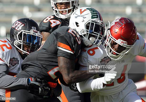 National running back from Virginia Taquan Mizzell is tackled by defensive back from St Francis Lorenzo Jerome and cornerback from Houston Brandon...