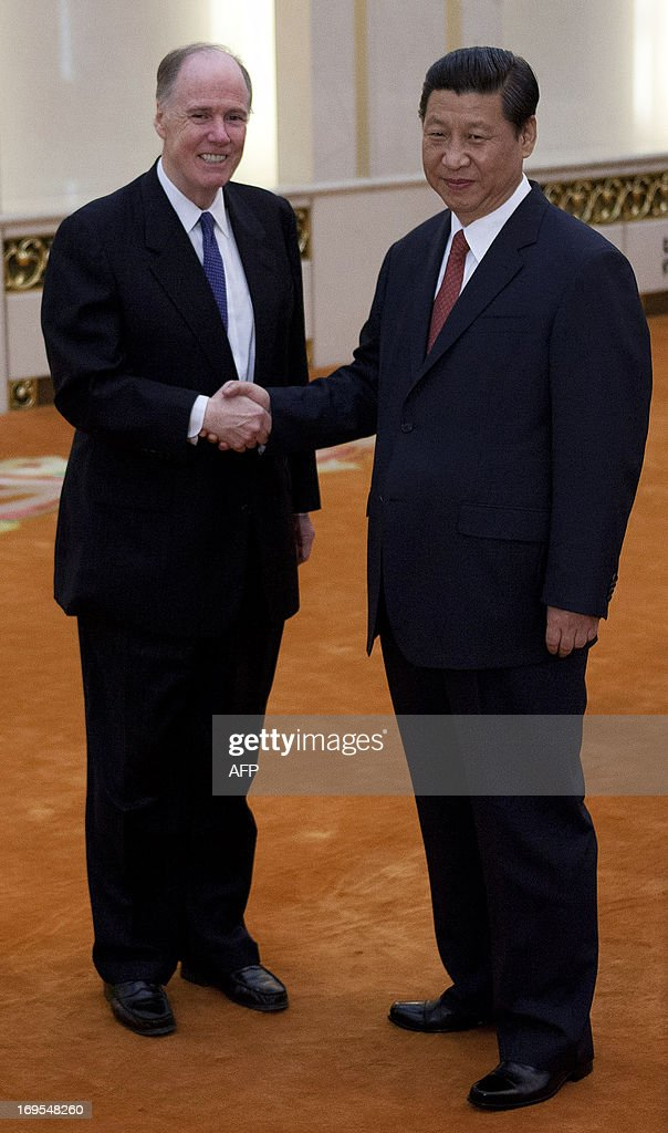 US National Security Adviser Tom Donilon (L) shakes hands with Chinese President Xi Jinping before their meeting at the Great Hall of the People in Beijing on May 27, 2013.