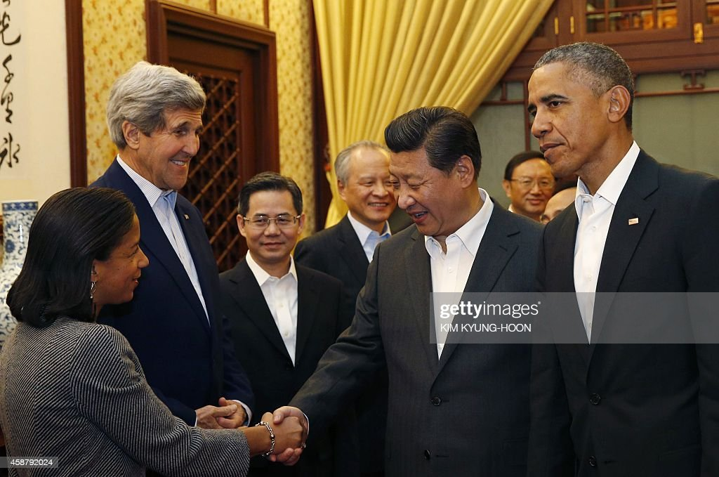 US National Security Advisor Susan Rice shakes hands with China's President Xi Jinping as US Secretary of State John Kerry and US President Barack...
