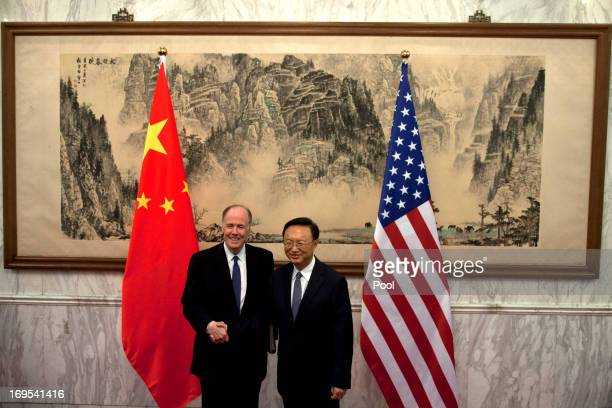 US National Security Advisor Tom Donilon and Chinese State Councilor Yang Jiechi shake hands before their meeting at Diaoyutai State Guesthouse on...