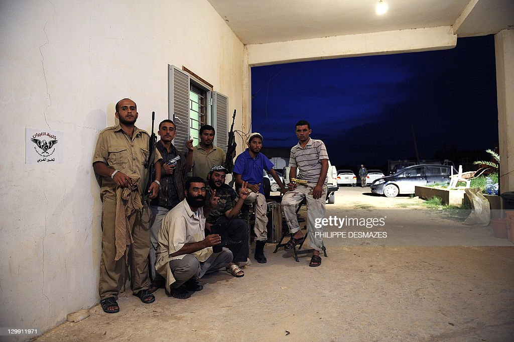 National Transitional Council (NTC) fighters from the Al-Ghiran brigade, who captured Libya's strongman Moamer Kadhafi on October 20 in Sirte, pose for a picture on October 21, 2011 at a farm on the outskirts of Misrata where they proudly exhibit the ousted leader's black boots, gold-plated gun and beige scarf. AFP PHOTO/PHILIPPE DESMAZES