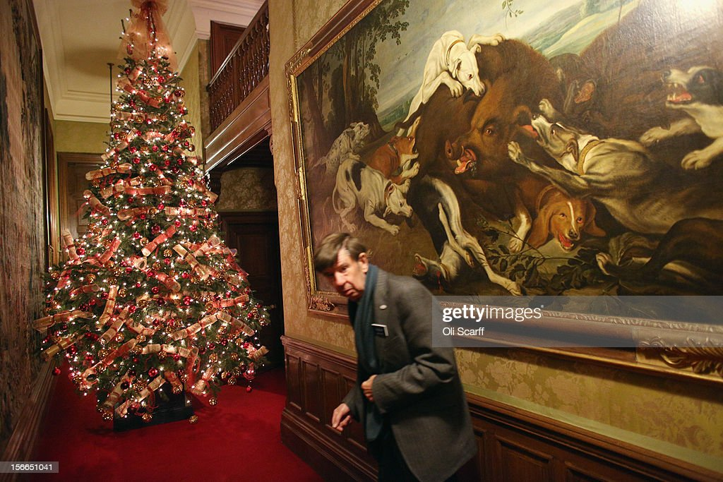 A National Trust employee walks past the Christmas decorations on the tree in the Bedroom Corridor of Waddesdon Manor on November 16, 2012 in Aylesbury, England. The East Wing and Bachelor's Wing of Waddesdon Manor have been elaborately decorated for Christmas in the theme of English traditions and literature. The light-artist Bruce Munro has also created two installations in the grounds of the manor. The Christmas decorations at Waddesdon Manor are open to the general public until January 1, 2013.