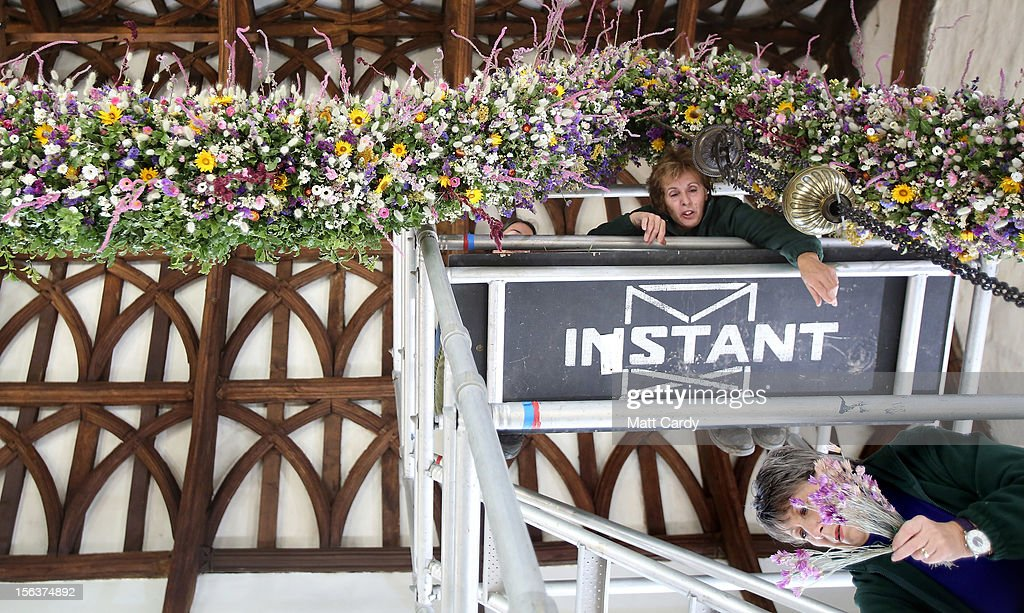 National Trust volunteer Carolina Hobbs (L) and volunteer Christina Payne (R) help create the Cotehele Christmas garland at the National Trust's Cotehele Tudor house, on November 14, 2012 in Cornwall, England. At 60ft (18.2 meters) the Cotehele garland - a tradition that was started in the 1950s and is created by using flowers picked and dried in the grounds of the Tudor mansion - is the longest at any Trust property in the country. Using flowers such as Ornamental Grasses, Everlasting Sand Flower, Straw Flower, Paper Daisy, Paper rose and Statice, the poor summer weather has meant that only 20,000 flowers have been picked this year rather than the usual 30,000.