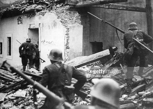 Nationalist troops loyal to General Franco advance bayonets fixed through the debris of houses at Madrid wrecked in air raids during the Spanish...