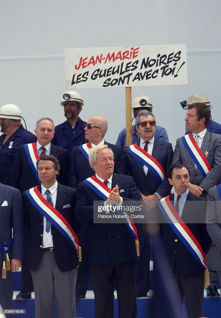 Nationql Front leqder, Jean-Marie Le Pen (C) attends the Fete de Jeanne d'Arc, or Festival of Joan of Arc, along with other extreme right-wing French leaders. A man in the rear with helmet, headlamp and face paint, holds a sign reading, 'Jean-Marie - the Black Faces Are with You,' in reference to Le Pen's racist politics.