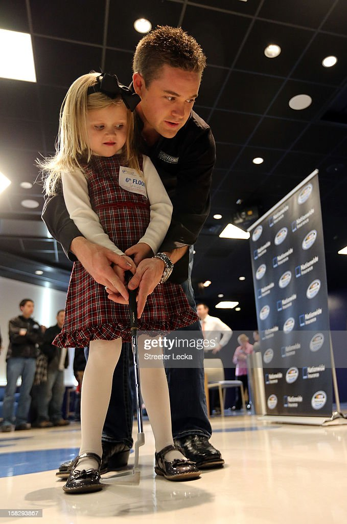 Nationwide Series Champion Ricky Stenhouse Jr. plays golf with patient Taylor Rockwell at the Nationwide Children's Hospital during the NASCAR Nationwide Series Champion's Day on December 12, 2012 in Columbus, Ohio