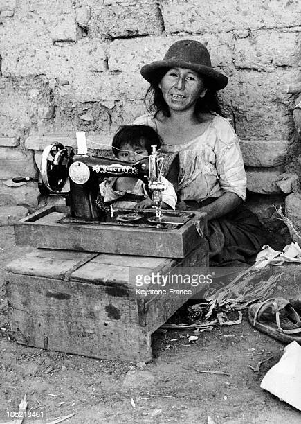 Native American And Her Child Seated Behind A Singer Sewing Machine In Bolivia On August 9 1967