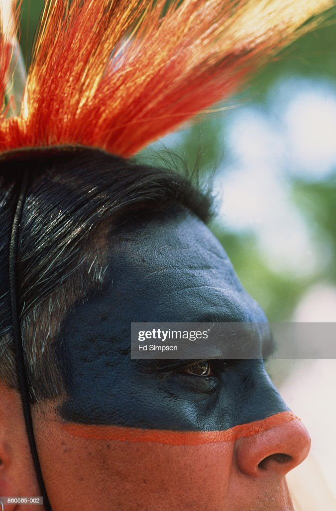 Native American Crow Indian man wearing head-dress and face paint : Stock Photo