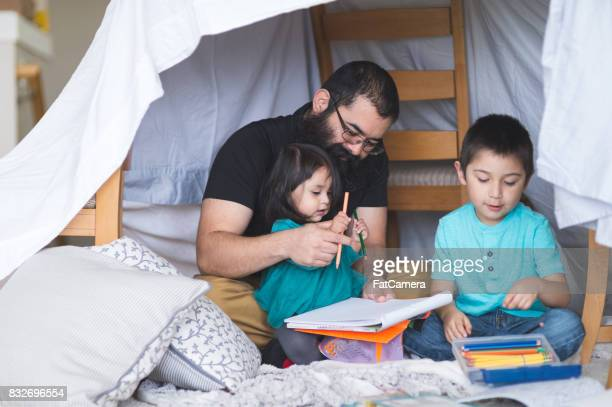 Native American dad draws with his two young children under makeshift fort in living room