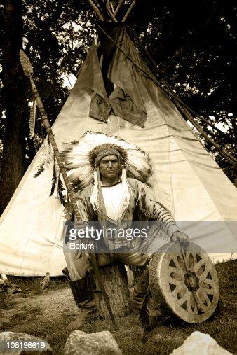 Nativos americanos en vestido tradicional de estar exterior tipi