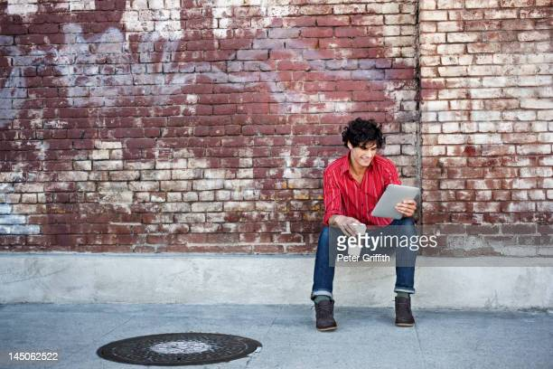 Native American man drinking coffee and using digital tablet in urban area