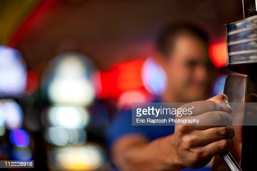Native American man pulling lever of slot machine in casino