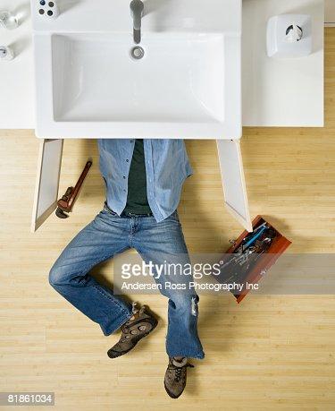 Native American man repairing bathroom sink