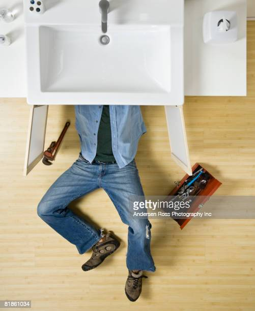 Native American man repairing bathroom sink