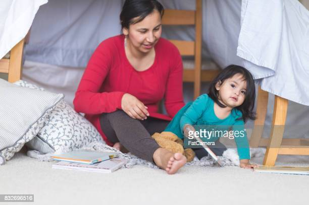 Native American mom and young daughter reading under their indoor blanket fort