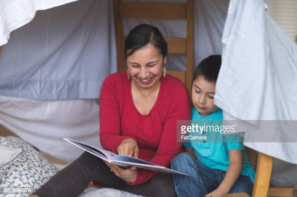 Native American mom reads with her son under makeshift fort in living room