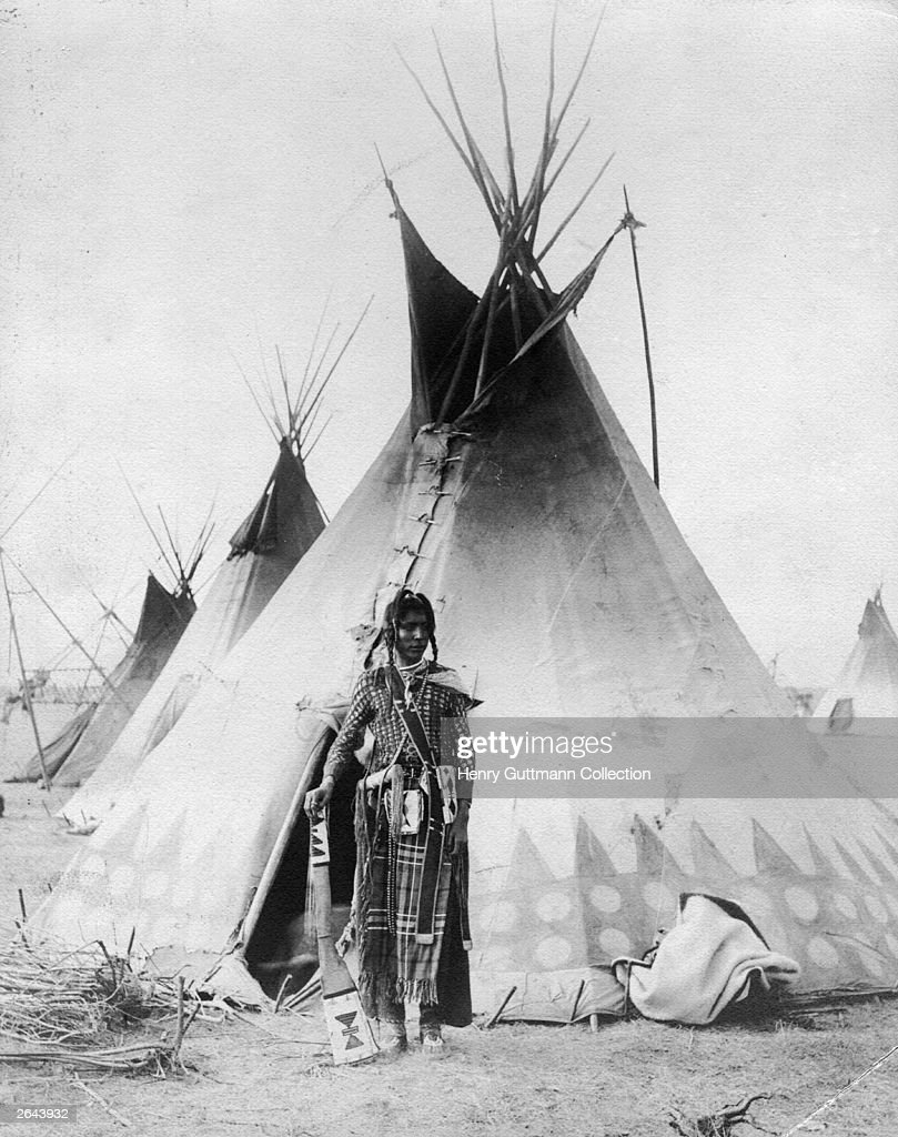 A Native American of one of the Great Plains tribes standing in front of his tepee