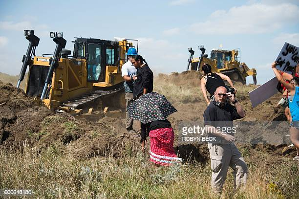 A Native American protestor refuses to move as other protestors opposed to the Dakota Access Pipeline rush towards bulldozers working on the new oil...