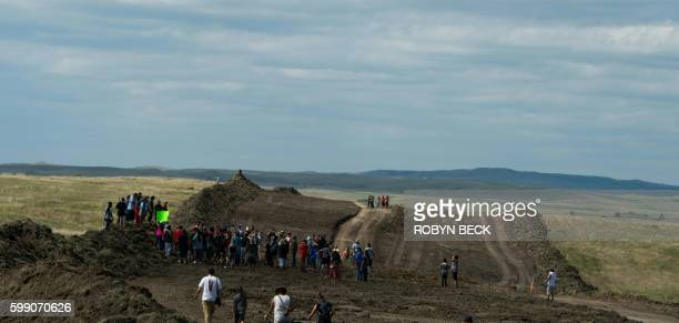 Native American protestors and their supporters walk along land being prepared for the Dakota Access Pipeline after protestors confronted contractors...