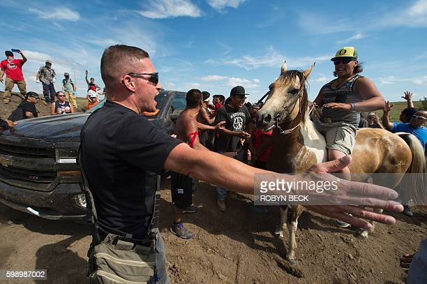 A Native American protestors holds up his arms as he and other protestors are threatened by private security guards and guard dogs at a work site for...