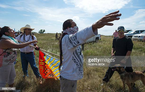 Native American protestors holds up his arms as he and other protestors are threatened by private security guards and guard dogs at a work site for...