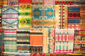 A collection of Native American rugs on display.
