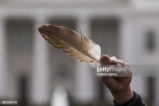 A Native American woman holds a feather a traditionally important item to Native Americans inner raised fist in front of the White House while...