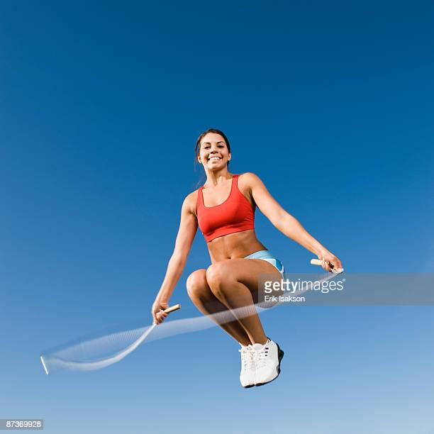 Native American woman jumping rope in mid-air